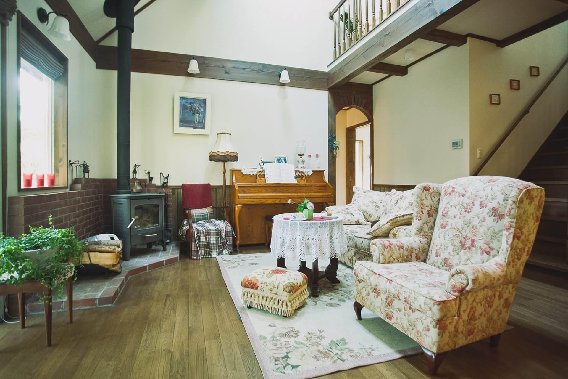 オフホワイトの壁とシックな茶系でまとめた梁、柱がアンティークの家具にしっくりとなじむ。吹き抜け部分には天窓からほどよい自然光が差し込んでいる